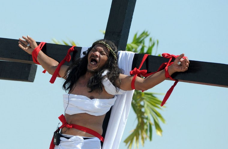 March 29, 2013: Philippine Christian devotee Ruben Enaje grimaces in pain after being nailed to the Cross by men dressed as Roman soldiers during a re-enactment of the crucifixion of Jesus Christ on Good Friday in San Fernando City, Pampanga province, north of Manila. (Noel Celis/AFP/Getty Images)