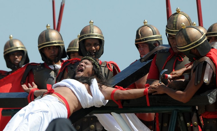 March 29, 2013: Philippine Christian devotee Ruben Enaje (C), grimaces in pain as he is nailed to the Cross by men dressed as Roman soldiers during a re-enactment of the crucifixion of Jesus Christ on Good Friday in San Fernando City, Pampanga province, north of Manila. (Noel Celis/AFP/Getty Images)