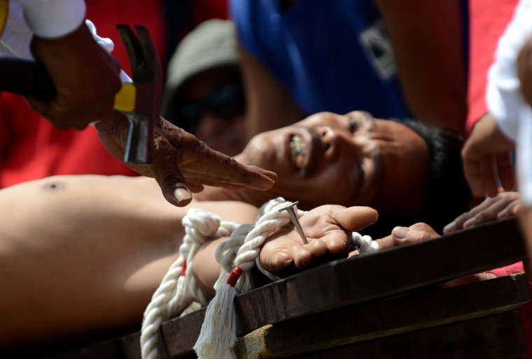 March 29, 2013: A penintent is nailed to a cross during the reenactment of crucifixion on Good Friday in the village of San Juan, San Fernando City, north of Manila. (Noel Celis/AFP/Getty Images)