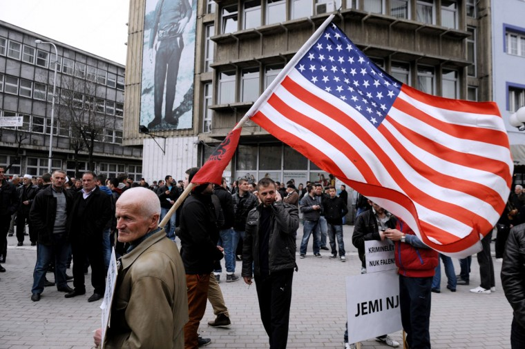 A Kosovo Albanian waves the US and Albanian flags while taking part in a protest on March 30, 2013 in the divided town of Mitrovica against the dialogue between Kosovo and Serbia. Kosovo's proclamation of independence is still not recognised by Serbia or by the 120,000-strong Serb minority in the breakaway territory. (Armend Nimani/AFP/Getty Images)