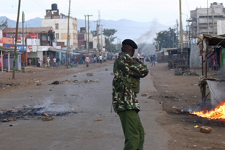 A policeman attempts to disperse rioters on March 30, 2013 on a street of outgoing Prime Minister Raila Odinga's stronghold lakeside city of Kisumu, where violence broke out after the ruling on of a petition hearing at the Kenya Supreme court in which Odinga challenged election contender Uhuru Kenyatta was delivered by a six-judge bench. Kenya's Supreme court on March 30 upheld the victory of Uhuru Kenyatta in the March 04, election Chief Justice, Willy Mutunga said. The court unanimously ruled that the election had been fair and credible and that Kenyatta and his running mate had been validly elected. (Tony Karumba/Stringer/AFP/Getty Images)
