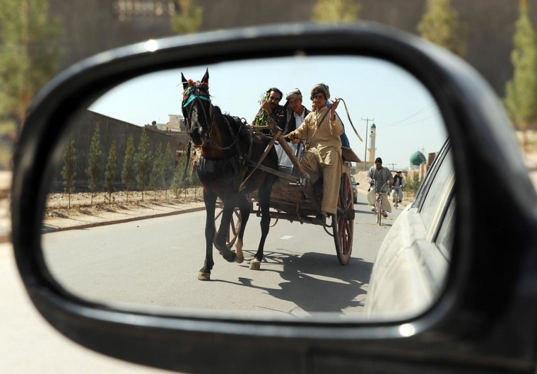"Afghan villagers are reflected mirror as they ride in a traditional cartalong a street in Herat on March 31, 2013. Some nine million Afghans or 36 percent of the population are living in ""absolute poverty"" while another 37 percent live barely above the poverty line, according to a UN report. (Aref Karimi/AFP/Getty Images)"