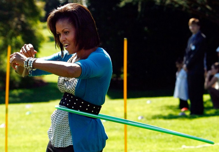 October 21, 2009: U.S. first lady Michelle Obama hula hoops on the South Lawn of the White House during an event promoting exercise and healthy eating for children in Washington, DC. The Healthy Kids Fair included events on cooking healthy meals and emphasized children getting a proper amount of outdoor exercise each day. (Win McNamee/Getty Images)