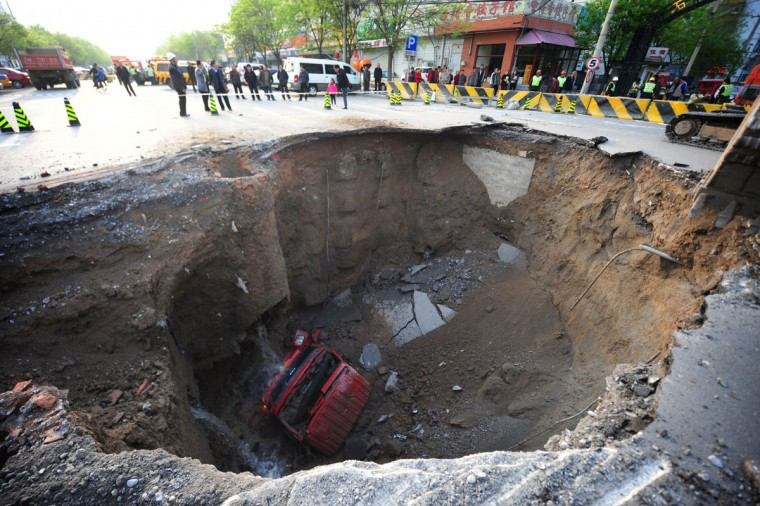 Workers block off the site of a huge sinkhole which occurred overnight in Shiliuzhuang road, in Beijing on April 26, 2011. A section of the road collapsed beneath a truck, slightly injuring the driver and a passenger, who both jumped out the vehicle before it sank into the hole. (STR/AFP/Getty Images)