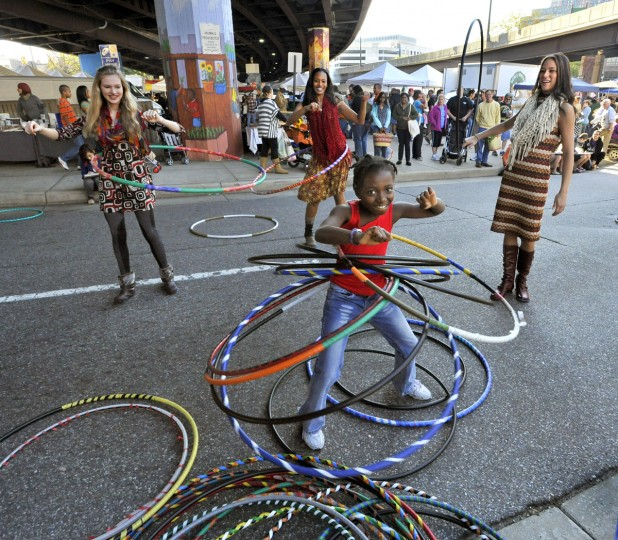 """October 9, 2011: Maimouna Diop, 8, demonstrates her hula hoops technique at Baltimore Hoop Love to Alex, left, Aneesah, center, and Chelsey, right. The Farmer's Market under the JFX is one of """"10 places to be seen"""" in Baltimore. (Amy Davis/Baltimore Sun)"""