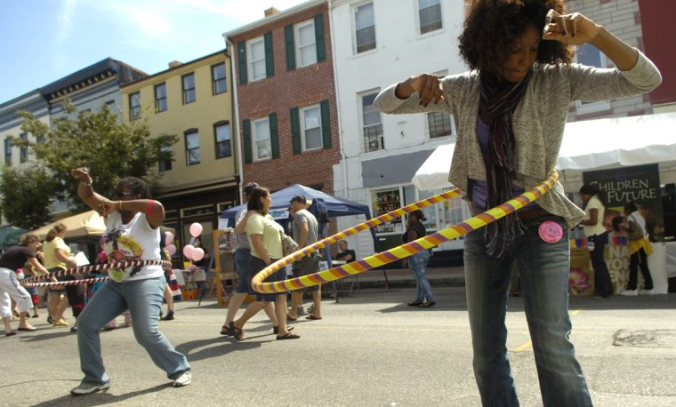 September 11, 2010: Anjelica Hebern, right, and Hazel Alexander, both with the Buddhist group Soka Gakkai International, perform with hula hoops during the Pigtown Festival. (Brian Krista/Baltimore Sun)