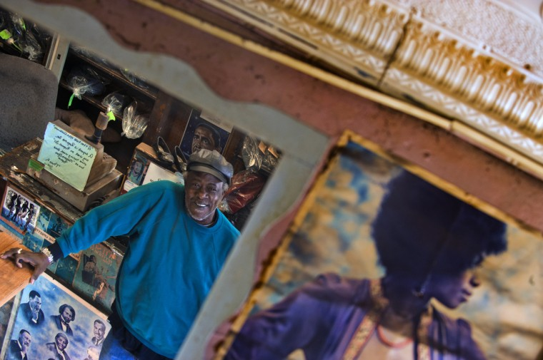 Malcolm Spaulding is reflected in a wall mirror, next to the very first image he secured to the walls of his corner shop in West Baltimore. (Karl Merton Ferron/Baltimore Sun)