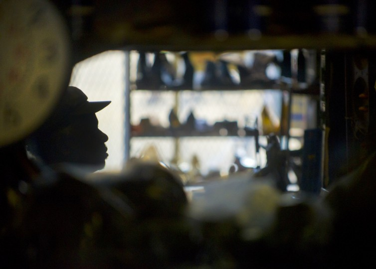 Malcolm Spaulding is reflected in a wall mirror at his corner shop in West Baltimore. Spaulding has been mending shoes for close to half a century. He started around 1960 as a boy in Kingston, Jamaica, when his father told him to go learn a trade. Cobbling is what he learned.(Karl Merton Ferron/Baltimore Sun)