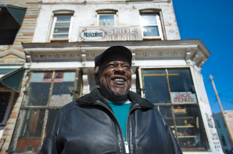 Malcolm Spaulding smiles outside his corner shop in West Baltimore. The business he's kept for 37 years ends March 15, when he retires and the building is prepared to be sold. (Karl Merton Ferron/Baltimore Sun)
