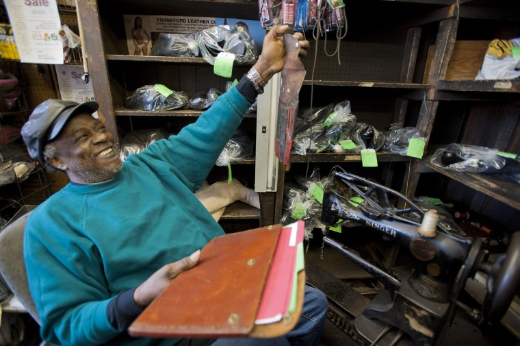 Malcolm Spaulding smiles, holding a leather folder and knife sheath that he made in his corner shop in West Baltimore. Spaulding's sister spotted an ad seeking shoemakers willing to move to America. That is how he found himself in Baltimore, at 23, working for Selis Shoe Repair on Calvert Street. (Karl Merton Ferron/Baltimore Sun)