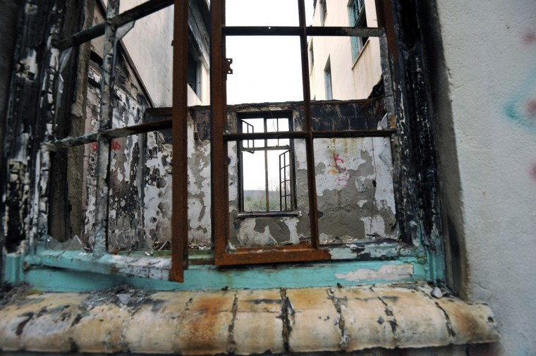 Broken and rusted window panes give a view into the dilapidated ruins of Henryton hospital. in the 35-building complex, according to information on file at the Maryland Historical Trust. It was converted in 1962 to a residential facility for the developmentally disabled, and closed nearly three decades ago. Kim Hairston/Baltimore Sun Staff. #4748.