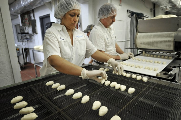 Blanca Gomez gives egg shaped vanilla butter cream room on a belt as Michael Wetzel runs the extruder. The soon to be chocolate enrobed eggs will be used in the Mary Sue Candies Bunny BonanZoo at the Maryland Zoo in Baltimore. (Kim Hairston/Baltimore Sun)