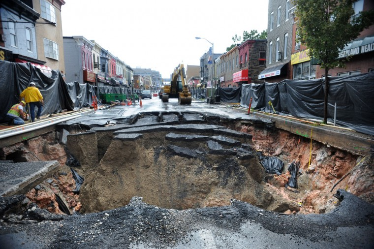 A large sinkhole opened on East Monument Street in Baltimore in summer 2012. The sinkhole appeared above a 120-year-old drainage culvert after heavy rains, causing evacuations and closing the road. (Algerina Perna/Baltimore Sun Photo)