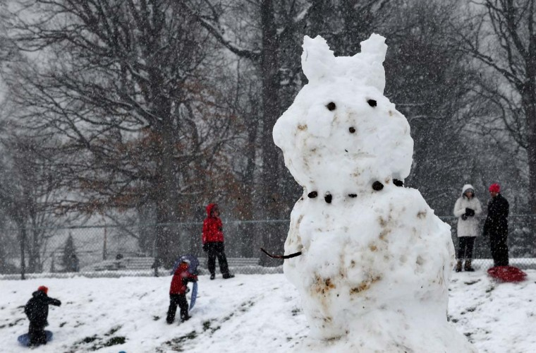 """Children took advantage of a snow day by sledding at Dumbarton Middle School under the watch of a very large """"Easter Snowman"""" in Maryland. (Algerina Perna/Baltimore Sun)"""