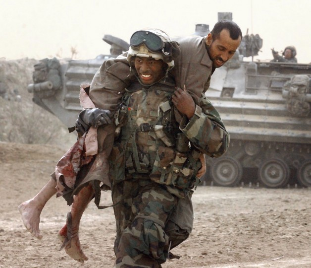 U.S. Marine Lance Corporal Marcco Ware, from Los Angeles, carries an injured Iraqi soldier who was shot three times during an attempted ambush of the 3rd Battalion , Fifth Regiment convoy Tuesday morning. One Marine was killed, one injured during the attack which resulted in about 40 dead Iraqi soldiers and thirty POW's. (John Makely/Baltimore Sun)