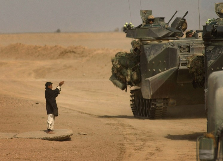 An Iraqi boy begs for food as an armored convoy from the Fifth Marines passes through the Iraq desert Saturday afternoon. (John Makely/Baltimore Sun)