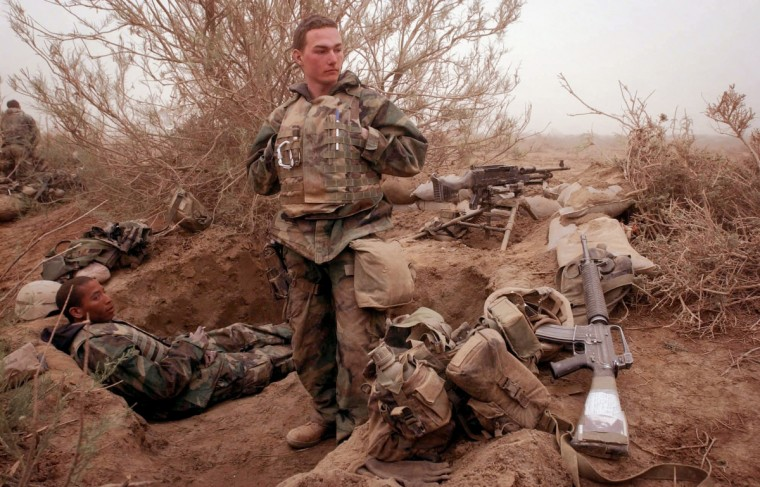 MARCH 26, 2003 -- PFC Keith Pelton, 19, of St. Clair, Missouri , stands in his foxhole with his machine gun Corporal Bryson Medlock, left, a day after their company was ambushed by Iraqi soldiers. Pelton, fresh out of boot camp, had his first confirmed kill, shooting an Iraqi Captain in the head during the Marines counter-attack. (John Makely/Baltimore Sun)