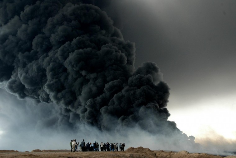 Iraqis watch the fire that broke out on Iraq's oil export pipeline from the southern city of Basra, 500 kilometres (300 miles) from Baghdad, to the Faw peninsula on the Gulf, 24 March 2004, in the Maamer zone 100 kilometers (62 miles) further south of Basra. A spokesman for the governorate of Basra said a technical problem caused the blaze. Basra is headquarters to some 8,800 British troops who have occupied the south of Iraq since last year's invasion which toppled president Saddam Hussein. (Joseph Barrak/Getty Images)