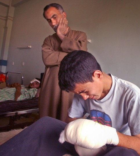 At the only working hospital in the Baghdad area, Mustafa Alkaiysi, 14, cries in his hospital bed as his father Kadhum Alkaiysi looks on. Mustafa's hands were badly injured when he picked up a denotator left behind by Fedayeen fighters at a school. (John Makely/Baltimore Sun)