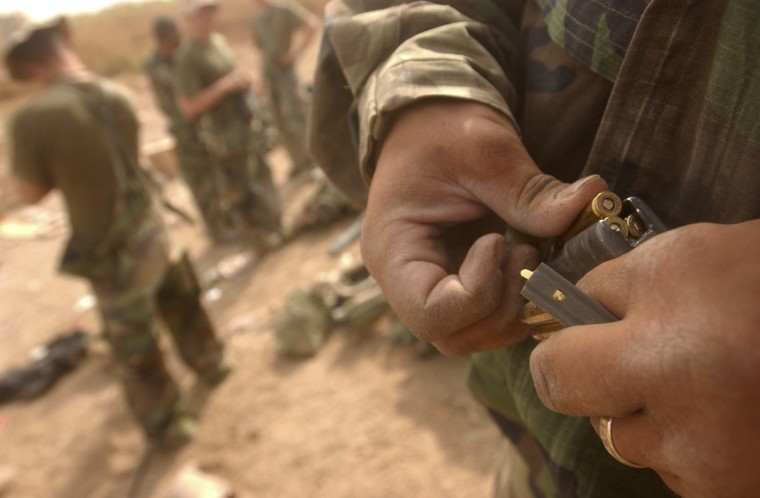 Al Aziziyah, Iraq -- April 3, 2003 -- While others brush their teeth, or have a bit of coffee, a Marine reloads his M-16 magazine. The weapons and their readiness come first. (John Makely/Baltimore Sun)