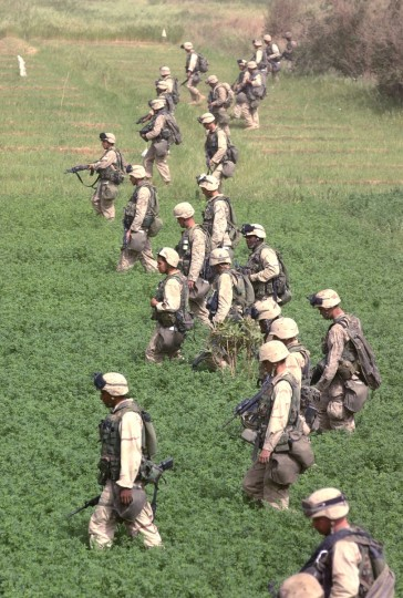 Baghdad, Iraq -- April 9, 2003 -- About ten miles east of downtown Baghdad, U.S. Marines of India Company, 3rd Battalion, 5th Regiment search a field for weapons near several 155 howitzer artillary pieces abandoned by Republican Guard forces. (John Makely/Baltimore Sun)