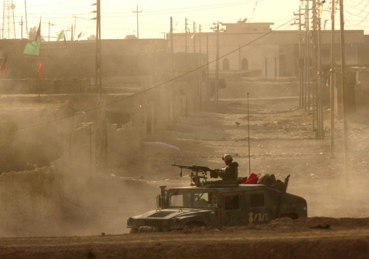 Al Aziziyah, Iraq -- April 3, 2003 -- Elements of the 3rd Battalion, 5th Marine regiment search the town of Al Azaziyah. An unspecified number of soldiers with the Republican Guard were captured and a cache of muntions dicovered in a school was destroyed. (John Makely/Baltimore Sun)