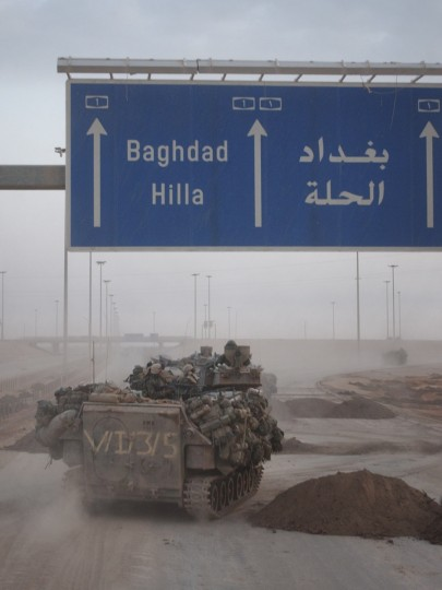 Ad Diwaniyah, IRAQ -- MARCH 30, 2003 -- An AAV with the the 3rd Battalion, Fifth Regiment travels under a highway sign as they move to new positions on their way north. (John Makely/Baltimore Sun)