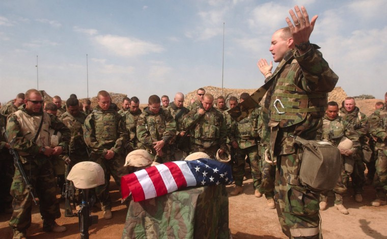 Ad Diwaniyah, IRAQ -- MARCH 29, 2003 -- U.S. Marine Corps chaplain Mark Tanis leads soldiers with the 3rd Battalion, Fifth Marines in prayer during a memorial service in honor of Major Kevin Nave and Corpsman Michael Johnson . Johnson was killed when an Iraqi fired rocket propelled grenade impacted his vehicle during the ambush on Tuesday and Nave died when a Marine Amphibious Assault Vehicle drove over him in his foxhole early Wednesday. (John Makely/Baltimore Sun)