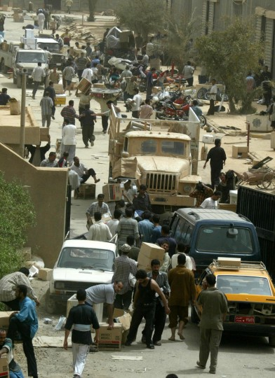 Iraqis loot the oil ministry storage facility in Baghdad 09 April 2003. US troops have entered without resistance overnight into the teeming northeast Shiite suburb where massive acts of looting were reported in the morning, witnesses reported. Fighting was reported in other parts of the city. (Ramzi Haidar/Getty Images)