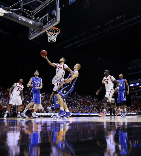 Louisville guard Peyton Siva (3) goes past Duke forward Mason Plumlee (5) for this bucket in second half action in the NCAA regional final game on Sunday, March 31, 2013, in Indianapolis, Indiana. Louisville won the game 85-63 in the NCAA regional final game. (Sam Riche/MCT)