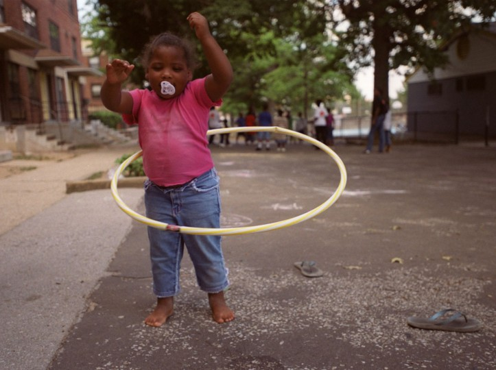 August 7, 2002: Youth ambassadors of the Safe and Sound campaign take to some of Baltimore's worst streets to make playgrounds out of vacant lots. Brittany Newman, 4, plays with the hula hoop outside her home at the corner of Mount Avenue and Laurens Street. (Nanine Hartzenbusch/Baltimore Sun)