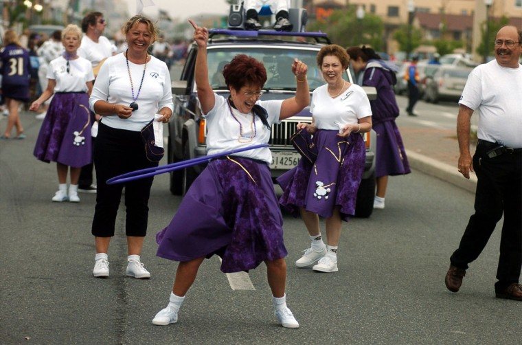 """June 5, 2004: Janis Speranzella, White Marsh, shows off her hula hoop skills as she marches with fellow Roost 52 members in The Council of Baltimore Ravens Roosts parade on Baltimore Ave. Roost 52 meets in White Marsh and this is one of the events in the council's weekend-long annual convention. The theme of the convention is """"Rockin' N Raven in Ocean City."""" (Kim Hairston/Baltimore Sun)"""