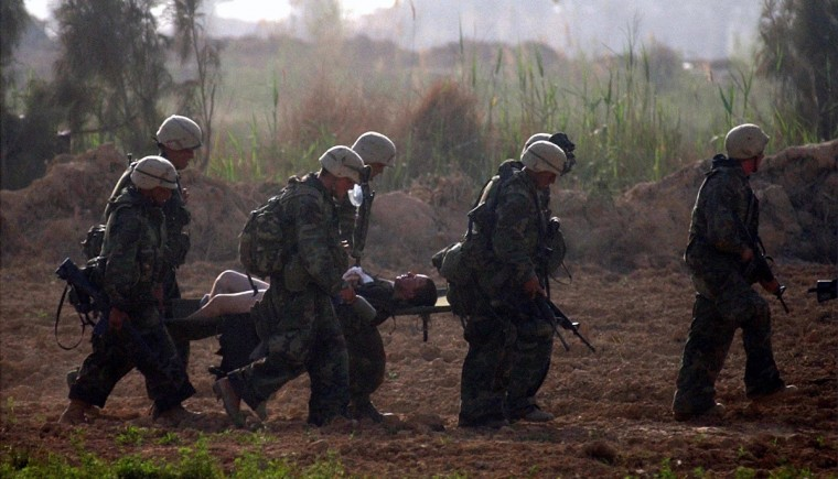 Al Muhaydi As Salih, IRAQ -- April 4, 2003 -- USMC Lance Corporal Mike Meyer is evacuated by stretcher after he was shot eight times during an intense firefight twenty miles south of Baghdad as part of India company, Third Battalion, Fifth Marine Regiment. (John Makely/Baltimore Sun)