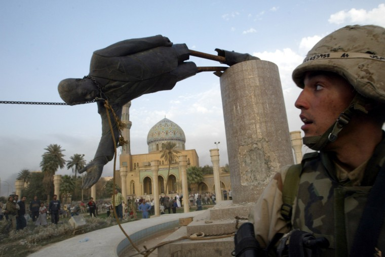 A U.S. soldier watches as a statue of Iraq's President Saddam Hussein falls in central Baghdad in this April 9, 2003 file photo. (Goran Tomasevic/Reuters photo)