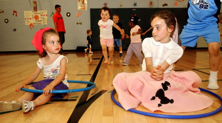 """May 14: 2004: Sisters Erica and Kayla Morton give each other a look as they wait for the Hula Hoop competition to begin during the PTA sponsored """"Sock Hop"""" at Bryant Woods Elementary School. (Reid Silverman/Patuxent Publishing)"""