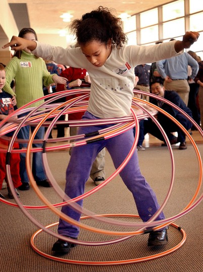 January 11, 2003: Nine-year-old Abra Roberts of Owings Mills shakes her hips to keep ten hula-hoops whirling arounds her hips. She was among hundreds of kids who attended the children's celebration for Governor-elect Robert Ehrlich's inauguration at Howard Community College. (Francis Gardler/Patuxent Publishing)