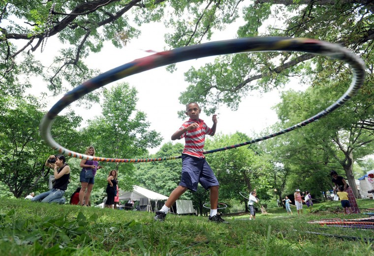 June 6, 2010: Cole Jarrett, 10, of Owings Mills plays with a giant hula hoop at the Charles Village Festival. He stopped there with his family on the way home from Greater Gethsemane Missionary Baptist Church in Baltimore. (Steve Ruark/Patuexent Publishing)