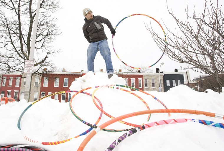 """February 13, 2012: Andreas """"Spilly"""" Spiliadis of Oakenshawe hula hoops on top of a mound of snow during the 33rd Street Farmers Market on . Spiliadis typically visits the market each week and hula hoops in the median of 33rd Street, but relocated due to the snowstorms that slammed Baltimore the previous week. (Sarah Pastrana/Patuxent Publishing)"""