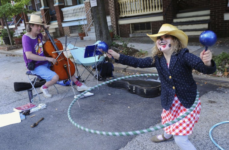 September 23, 2012: During a break from playing his recorder and flute with his band Henrietta Street, Marlin Ballard, Jr., of Cockeysville, plays a cello for the first time as Grace Dworkin, 8, of Homeland, plays maracas while hula hooping at the annual street fair on Abell Street in Charles Village. (Karen Jackson/Patuxent Publishing)