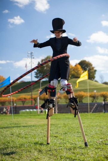 October 21, 2012: Lynn Tomlinson, of Catonsville, tries to use a giant hula-hoop while she wears stilts. The 2nd Annual Stiltathon was held on Rash Field in the Inner Harbor. Molly Ross, a performance artist from Hampden organized the event with her company Nana Projects. Stilting workshops were offered in the earlier part of the day with more experienced people showing up later to hangout, dance and hula-hoop on stilts for visitors. (Nate Pesce/Patuxent Publishing)