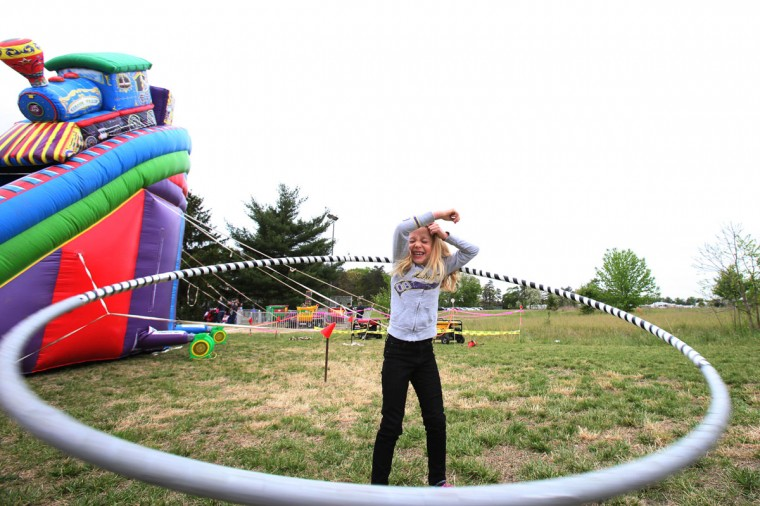April 28, 2012: Riley Bateman, 6, of Fort Meade laughs while attempting to hula hoop with an oversized hoop during Family Fun Day in McGill Training Center at Fort Meade on Saturday. (Jen Rynda/Patuxent Publishing)