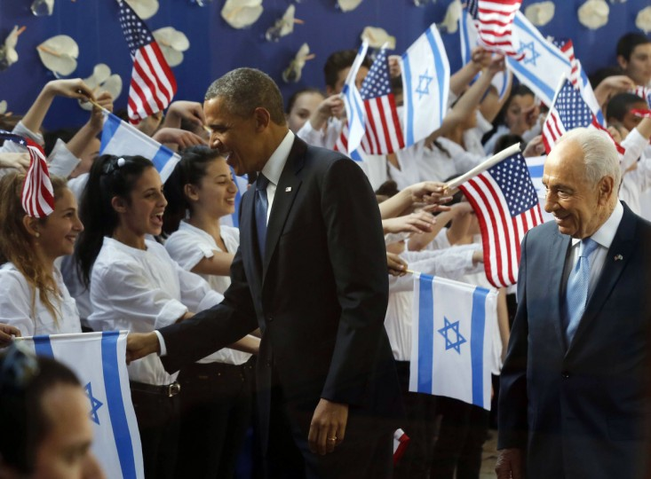 U.S. President Barack Obama shakes hands with children next to Israel's President Shimon Peres at his residence in Jerusalem. Making his first official visit to Israel, Obama pledged on Wednesday unwavering commitment to the security of the Jewish State where concern over a nuclear-armed Iran has clouded U.S.-Israeli relations. (Larry Downing/Reuters)