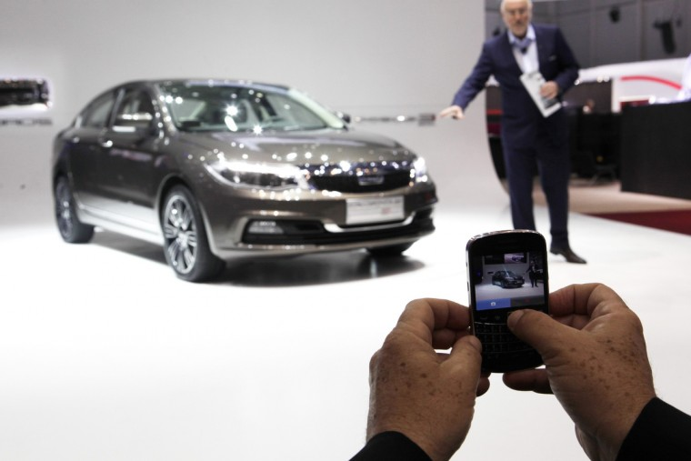 A man takes a picture using a mobile phone while Qoros Designer Gert Hildebrand presents the new Qoros 3 Sedan car during the first media day of the 83rd Geneva Car Show at the Palexpo Arena in Geneva. Chinese-Israeli carmaker Qoros announced its entry into Europe on Tuesday, the latest attempt by a Chinese manufacturer to gain a foothold in the region's highly competitive market. (Denis Balibouse/Reuters photo)