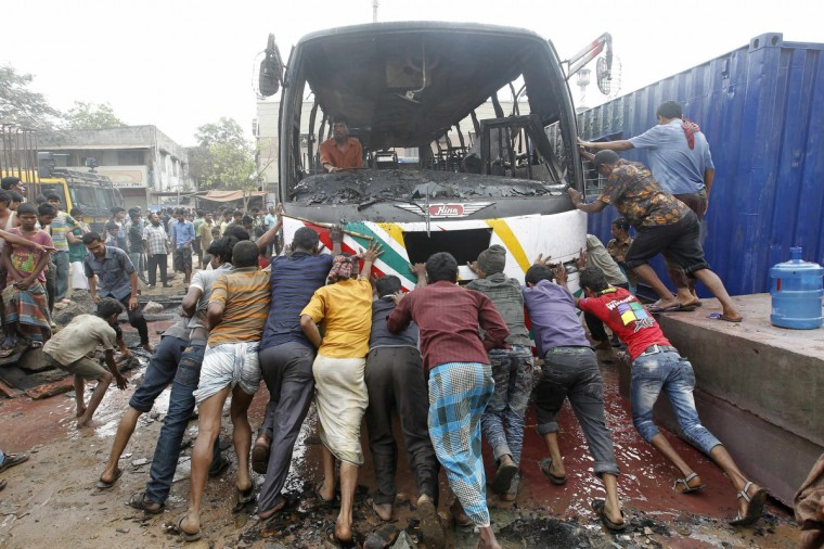 People help a driver to move his bus after activists of the Bangladesh Nationalist Party (BNP) set fire to it during a nationwide strike in Dhaka. Police on Monday arrested more than 200 opposition leaders, including BNP acting secretary general Mirza Fakhrul Islam Alamgir following a violent clash in front of their party office. The BNP announced a nationwide dawn-to-dusk shutdown on Tuesday, claiming that Monday's raid on the BNP office was an attack on the opposition 18-party rally, local media reported. (Andrew Biraj/Reuters)