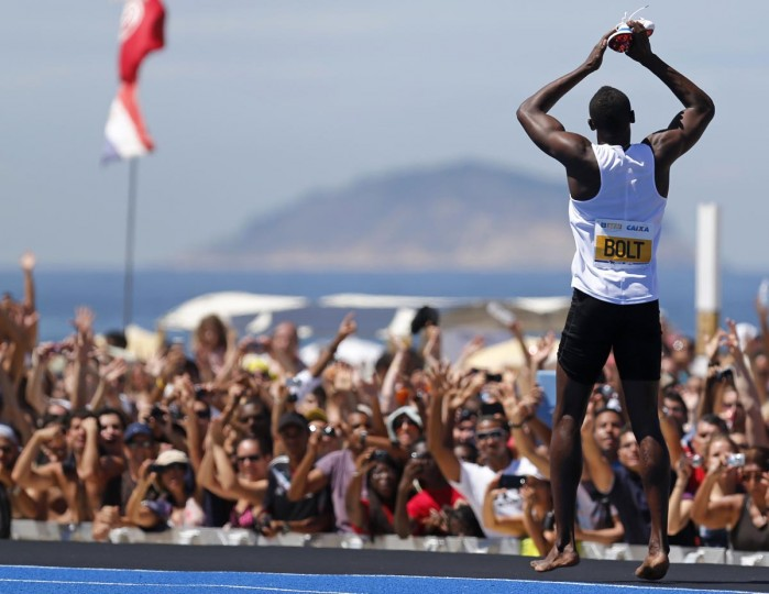"Jamaican Olympic gold medallist Usain Bolt celebrates after winning the ""Mano a Mano Men's 150 metres"" challenge on Copacabana beach in Rio de Janeiro March 31, 2013. (Sergio Moraes/Reuters)"