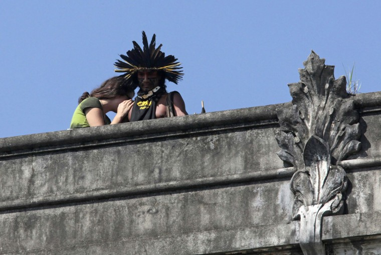 A native Indian and a supporter react as they observe police officers from the roof of the Brazilian Indian Museum in Rio de Janeiro. Brazilian military police took position early morning outside the abandoned Indian museum, where a native Indian community of around 30 individuals have been living since 2006. The group is fighting against the destruction of the museum, which is next to the Maracana Stadium. (Sergio Moraes/Reuters)