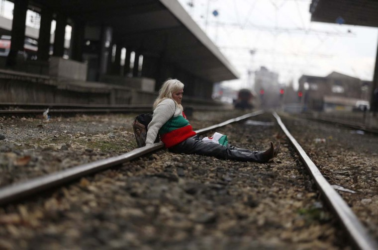 A protester, wearing a sweater in the colours of the Bulgarian national flag, sits on the tracks as demonstrators block the main railway station in Sofia March 10, 2013. Hundreds of Bulgarians took to the streets for a fourth Sunday in a row against monopolies and widespread corruption, demanding a stop to the planned sale of the cargo unit of ailing state railway operator BDZ and an audit of all privatisation deals. (Stoyan Nenov/Reuters)