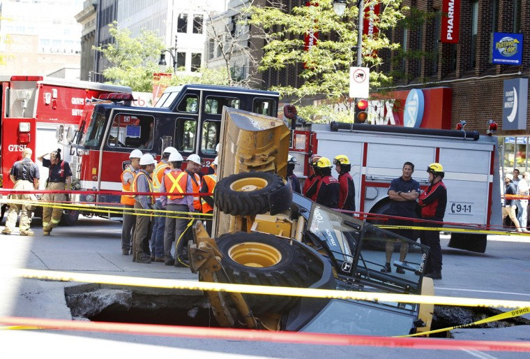 A construction vehicle lies where it was swallowed by a sinkhole on Saint-Catherine Street in downtown Montreal, August 5, 2013. (Christinne Muschi/Reuters photo)
