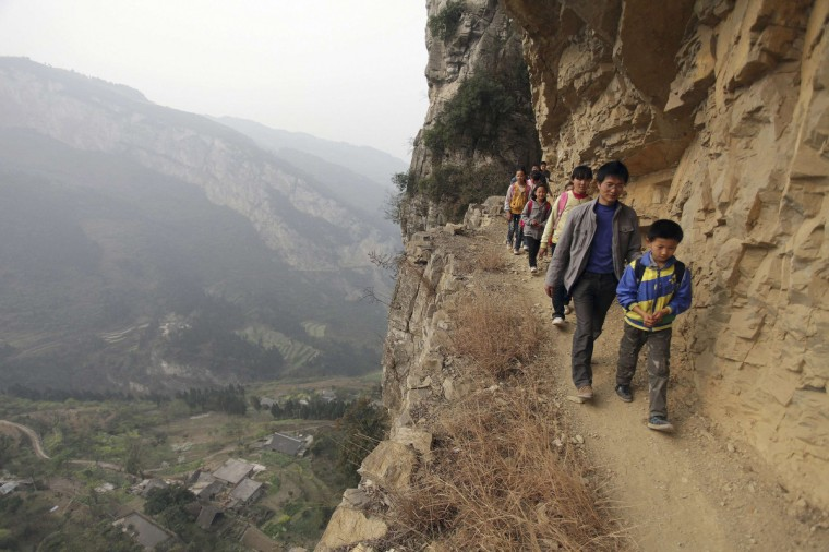 Xu Liangfan, 37, escorts students on a cliff path as they make their way to Banpo Primary School in Shengji county, Bijie city in Guizhou province. Xu, who started working at the school last year, is the headmaster of the school and teaches mathematics and gym class. Located halfway up a mountain, the school has 68 students of which about 20 live in the nearby Gengguan village. Students from Gengguan have to edge their way along the narrow cliff path to go to class everyday, alongside Xu who would escort them. The path, which was carved from cliffs over 40 years ago, is the only route between Gengguan village and the school, according to local media. (Reuters)