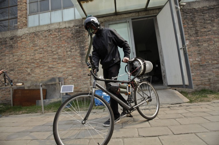 """Artist Matt Hope, wearing a helmet, pushes his air filtration bike out from his studio on a hazy day in Beijing. Using an IKEA perforated garbage can, moped helmet, fighter-pilot breathing mask, wheel-powered generator and home air filtration system, Beijing-based artist Matt Hope built a """"breathing bicycle"""" as a way of protecting himself from air pollution. While pedaling, electricity is generated for the power to activate the system to filter out haze and provide the rider with clean air, local media reported. According to the U.S. embassy monitor, the air quality today is classified as """"very unhealthy"""". (Petar Kujundzic/Reuters)"""
